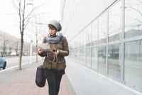 Female backpacker with smartphone looking at map on city sidewalk 11015320917| 写真素材・ストックフォト・画像・イラスト素材|アマナイメージズ