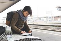 Female backpacker looking at map and digital tablet on railway platform 11015320921| 写真素材・ストックフォト・画像・イラスト素材|アマナイメージズ