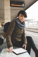 Portrait of female backpacker with map and digital tablet on railway platform 11015320923| 写真素材・ストックフォト・画像・イラスト素材|アマナイメージズ