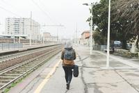 Rear view of female backpacker on railway platform 11015320925| 写真素材・ストックフォト・画像・イラスト素材|アマナイメージズ
