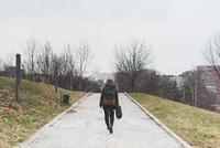 Rear view of female backpacker walking alone in city park 11015320936| 写真素材・ストックフォト・画像・イラスト素材|アマナイメージズ