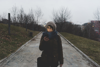 Female backpacker walking in city park at dusk looking at smartphone 11015320937| 写真素材・ストックフォト・画像・イラスト素材|アマナイメージズ