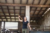 Female organic farmer with pitch fork over her shoulder on dairy farm 11015321001| 写真素材・ストックフォト・画像・イラスト素材|アマナイメージズ