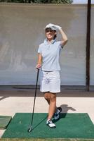Woman standing on turf with golf club 11015321057| 写真素材・ストックフォト・画像・イラスト素材|アマナイメージズ