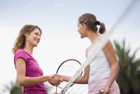 Girls shaking hands on tennis court 11015321527| 写真素材・ストックフォト・画像・イラスト素材|アマナイメージズ