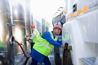 Workers filling trucks with gas 11015321581| 写真素材・ストックフォト・画像・イラスト素材|アマナイメージズ