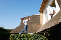 Girls watching boy play golf on roof 11015321655| 写真素材・ストックフォト・画像・イラスト素材|アマナイメージズ