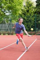 Boy playing tennis on court 11015321659| 写真素材・ストックフォト・画像・イラスト素材|アマナイメージズ