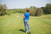 Boy swinging club on golf course 11015321660| 写真素材・ストックフォト・画像・イラスト素材|アマナイメージズ