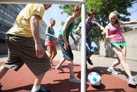 Friends playing soccer on city street 11015321677| 写真素材・ストックフォト・画像・イラスト素材|アマナイメージズ