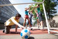 Friends playing soccer on city street 11015321679| 写真素材・ストックフォト・画像・イラスト素材|アマナイメージズ