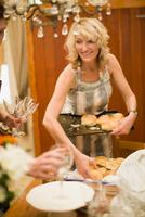 Woman placing bread rolls on tray 11015322011| 写真素材・ストックフォト・画像・イラスト素材|アマナイメージズ