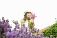 Woman gathering flowers in garden 11015322196| 写真素材・ストックフォト・画像・イラスト素材|アマナイメージズ
