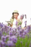 Woman gathering flowers in garden 11015322197| 写真素材・ストックフォト・画像・イラスト素材|アマナイメージズ