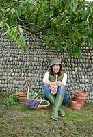 Woman with baskets of plants in garden 11015322198| 写真素材・ストックフォト・画像・イラスト素材|アマナイメージズ