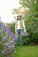 Woman gathering flowers in garden 11015322199| 写真素材・ストックフォト・画像・イラスト素材|アマナイメージズ