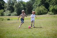 Children playing soccer in grassy field 11015323400| 写真素材・ストックフォト・画像・イラスト素材|アマナイメージズ