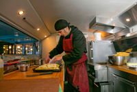 Chef preparing pizza in food stall van at night 11015325072| 写真素材・ストックフォト・画像・イラスト素材|アマナイメージズ