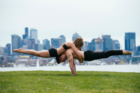 Young woman balancing on top of man in prone position, practicing yoga in front of Seattle skyline 11015325169| 写真素材・ストックフォト・画像・イラスト素材|アマナイメージズ