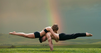 Young woman balancing on top of man in prone position, practicing yoga in front of rainbow 11015325170| 写真素材・ストックフォト・画像・イラスト素材|アマナイメージズ