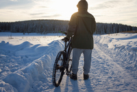 Rear view of male mountain biker watching sunset over snow covered landscape 11015325193| 写真素材・ストックフォト・画像・イラスト素材|アマナイメージズ
