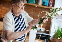 Senior adult woman with floral craftwork 11015325311| 写真素材・ストックフォト・画像・イラスト素材|アマナイメージズ
