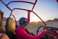 Young woman with head wrapped in scarf driving beach buggy in desert, Hurghada, Al Bahr al Ahmar, Egypt 11015325346| 写真素材・ストックフォト・画像・イラスト素材|アマナイメージズ