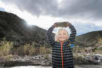 Portrait of cute boy holding up rock from riverbed 11015325394| 写真素材・ストックフォト・画像・イラスト素材|アマナイメージズ