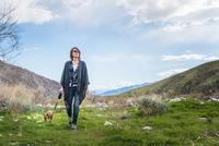 Mature woman walking dog in valley landscape 11015325397| 写真素材・ストックフォト・画像・イラスト素材|アマナイメージズ