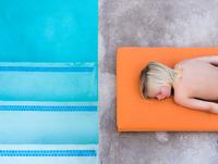 Overhead view of boy lying on poolside 11015325402  写真素材・ストックフォト・画像・イラスト素材 アマナイメージズ