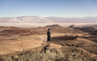 Man on rock looking out over Death Valley National Park, California, USA 11015325417| 写真素材・ストックフォト・画像・イラスト素材|アマナイメージズ