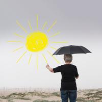 Senior woman with umbrella drawing sun in air 11015325491| 写真素材・ストックフォト・画像・イラスト素材|アマナイメージズ