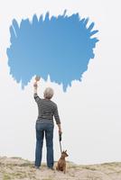 Senior woman with dog on lead painting blue sky in air 11015325492| 写真素材・ストックフォト・画像・イラスト素材|アマナイメージズ
