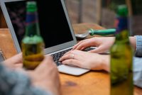 Cropped view of couple drinking beer using laptop 11015325604| 写真素材・ストックフォト・画像・イラスト素材|アマナイメージズ