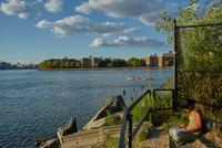 Woman reading on riverbank, New York, USA 11015325617| 写真素材・ストックフォト・画像・イラスト素材|アマナイメージズ