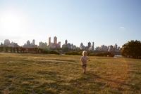 Boy running in park in front of New York skyline, USA 11015325618| 写真素材・ストックフォト・画像・イラスト素材|アマナイメージズ