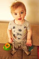 Portrait of cute male toddler standing on sofa 11015325619| 写真素材・ストックフォト・画像・イラスト素材|アマナイメージズ