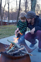 Boy and father tending fire in patio fire pit 11015325622| 写真素材・ストックフォト・画像・イラスト素材|アマナイメージズ