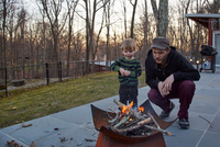 Boy and father tending fire in patio fire pit 11015325628| 写真素材・ストックフォト・画像・イラスト素材|アマナイメージズ