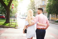 Rear view of couple walking in street arms around each other 11015325746| 写真素材・ストックフォト・画像・イラスト素材|アマナイメージズ