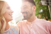 Portrait of couple in sunlight face to face smiling 11015325753| 写真素材・ストックフォト・画像・イラスト素材|アマナイメージズ