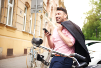 Man with bicycle holding smartphone smiling 11015325754| 写真素材・ストックフォト・画像・イラスト素材|アマナイメージズ