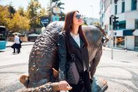 Woman beside street sculpture 11015325788| 写真素材・ストックフォト・画像・イラスト素材|アマナイメージズ