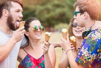Friends eating ice cream cones smiling 11015325861| 写真素材・ストックフォト・画像・イラスト素材|アマナイメージズ