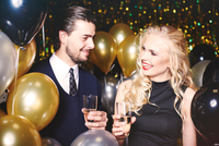 Young man and woman at party, holding champagne glasses, smiling 11015326118| 写真素材・ストックフォト・画像・イラスト素材|アマナイメージズ