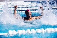 Swimmer in pool beating water in triumph 11015326446| 写真素材・ストックフォト・画像・イラスト素材|アマナイメージズ