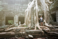 Portrait of young female tourist by tree roots at Ta Prohm temple, Angkor, Siem Reap, Cambodia 11015326499| 写真素材・ストックフォト・画像・イラスト素材|アマナイメージズ