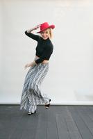 Portrait of mid adult female dancer dancing on wooden floor holding red fedora 11015326506| 写真素材・ストックフォト・画像・イラスト素材|アマナイメージズ
