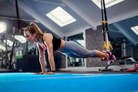 Young woman doing push ups using exercise handles in gym 11015327303  写真素材・ストックフォト・画像・イラスト素材 アマナイメージズ