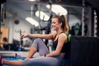 Happy young woman training, sitting on gym floor 11015327304  写真素材・ストックフォト・画像・イラスト素材 アマナイメージズ